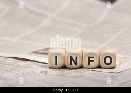 information concept - wooden cubes on newspaper forming word INFO - Stock Photo