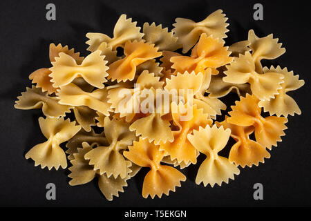 Colorful raw bow tie pasta on black background. Farfalle pasta - Stock Photo