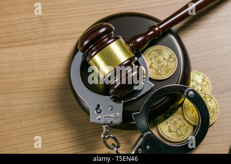 Gavel and handcuffs with bitcoins on wooden desk. Cryptocurrency legal concept. - Stock Photo
