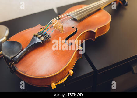The violin on the dark table, Close - up of violin on the wooden floor, Top view of violin musical on dark wooden floor, Vintage and classic musical Stock Photo