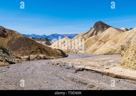 A dry rocky riverbed curves through a barren desert landscape of colorful badlands and peaks in Death Valley National Park