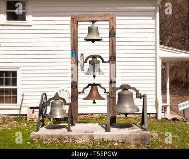 Marcellus , New York, USA. April 17, 2019. Antique bells on display behind  the Tefft-Steadman House in Marcellus, NY - Stock Photo
