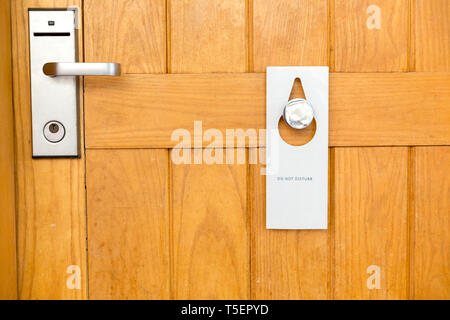 please do not disturb sign on Closed wooden door of hotel room. - Stock Photo