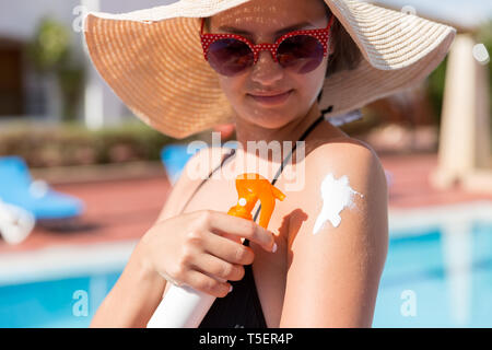 Caucasian woman putting solar cream on her shoulder by the pool under sunshine on summer day. Sun Protection Factor in vacation, concept. - Stock Photo