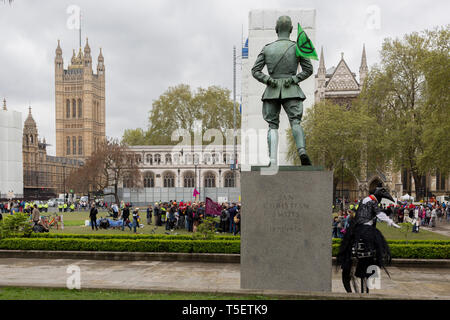 On the 10th consecutive day of protests around London by the climate change campaign Extinction Rebellion, a protester on stilts prepares to strut across Parliamant Square, on 24th April 2019, in Westminster, London England. - Stock Photo