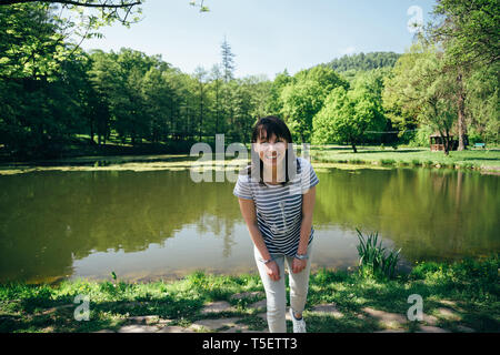 Tourist girl in blue jeans and striped shirt standing on the bank of the mountain lake surrounded by forest. - Stock Photo