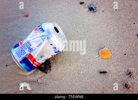 A Natural Light beer can lays on the beach, April 19, 2019, in Dauphin Island, Alabama. Most disposable cans like this are made from aluminum. - Stock Photo