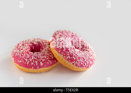 Two donuts with pink icing on a white background. - Stock Photo