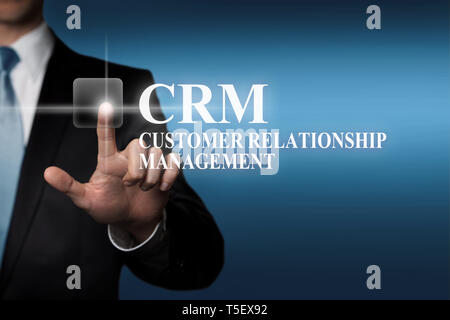 business concept - businessman presses virtual touch screen button - CRM Customer Relationship Management - Stock Photo