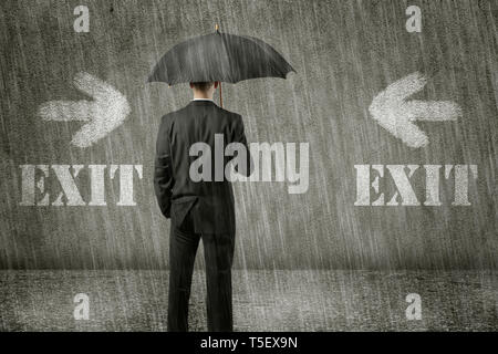Trapped unhappy businessman is standing in front of wall on a gloomy day and has no way out of his hopeless situation - business concept - Stock Photo