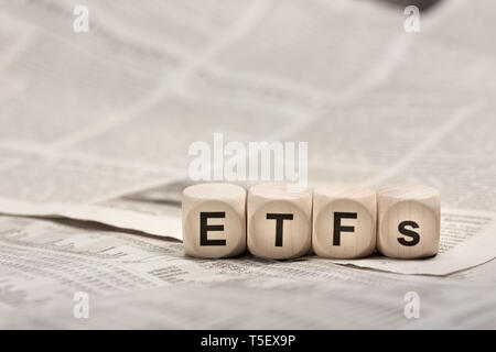 Exchange traded funds - wooden cubes on newspaper forming word ETFs - Stock Photo
