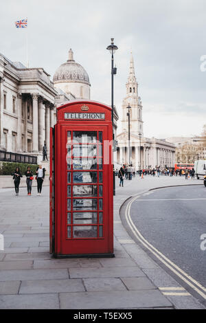 London, UK - April 13, 2019: Red phone box on Pall Mall East, National Gallery on the background. Red phone boxes can be found in current or former Br - Stock Photo
