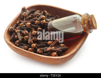 Fresh clove in bowl with oil in a jar over white background - Stock Photo