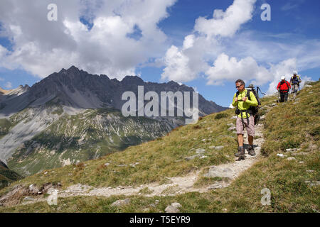 Pralognan-la-Vanoise (south-eastern France): group of hikers in the Vanoise National Park. Group of three men with backpacks, walking poles and hiking - Stock Photo