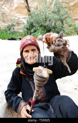 Old and weathered Bedouin woman spinning wool for weaving in Little Petra, Jordan. - Stock Photo