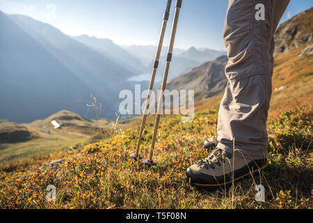 Hiking shoes and walking poles, with view over the dam of Tignes, the sheepfold and the refuge of La Martin, in the Vanoise National Park, Upper Taren - Stock Photo