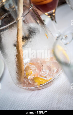 An empty jug of the Spanish drink Sangria - ice and lemon with stirrer seen in a glass jug. - Stock Photo