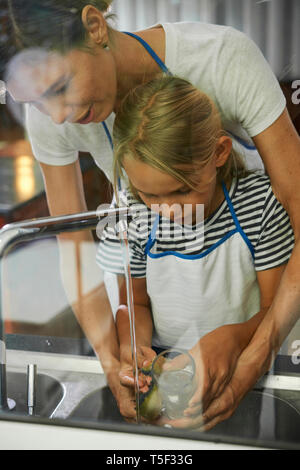 Mother and daughter watching dishes - Stock Photo