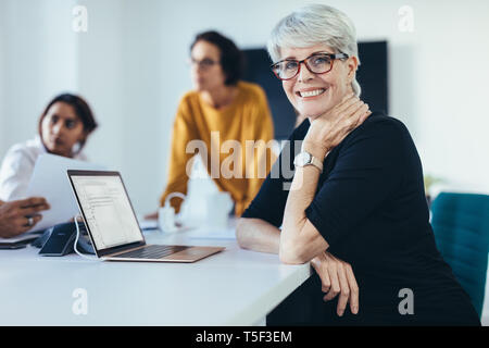 Successful mid adult woman sitting at a meeting with colleagues in boardroom. Female with coworkers in conference room looking at camera and smiling. - Stock Photo