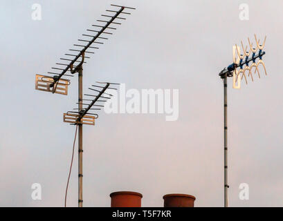 three tv aerials on a roof at sunset - Stock Photo