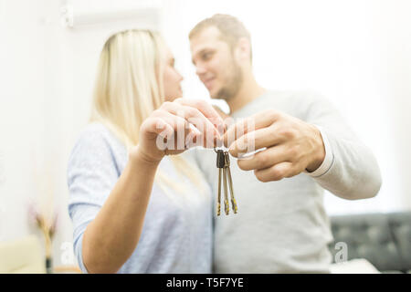A lovely young couple holds in front of them the keys to their new apartment. - Stock Photo