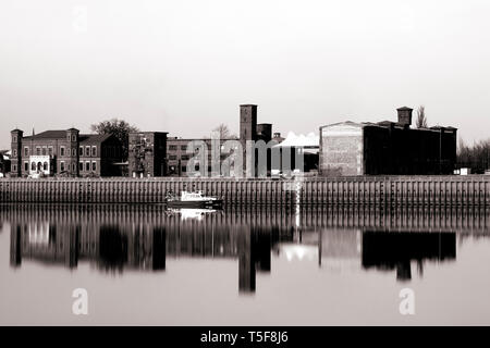 The photograph of an old industrial site on the river Elbe in Wittenberge with a passing police boat. - Stock Photo