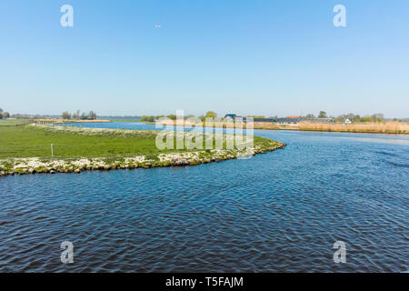 Landscape with waterways and canals of North Holland with boats, canal-side lifestyle in The Netherlands - Stock Photo