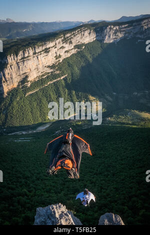 CHORANCHE, FRANCE - AUGUST 20: Two wingsuit jumpers jumping from a cliff in france, Auvergne-rhône-alpes, Choranche, France on August 20, 2015 in Choranche, France. (Photo by Fred Marie/Art in All of Us/Corbis via Getty Images) - Stock Photo