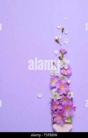 Creative concept. Paintbrush with cherry blossoms and purple flower on pastel purple background. Minimal nature composition with copy space.Flat lay,
