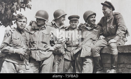 Meet Torgau (1945). American soldiers and Russian soldiers fraternize after their meeting on the river Elbe, at 140 km south of Berlin. - Stock Photo