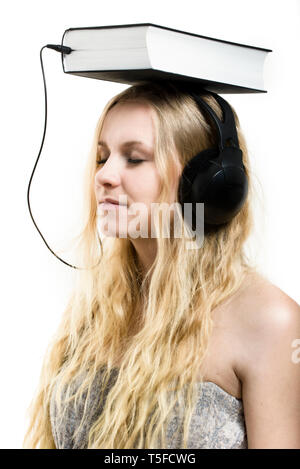 Audio book idea - a young woman with headphones connected to the book - Stock Photo