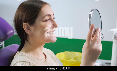 Young woman in dental chair examines her teeth in the mirror after treatment, side view. Teeth care concept. - Stock Photo