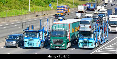 Looking down on hgv lorry truck & articulated trailer vehicles overtaking in  bunched up traffic on gradient busy four lane M25 motorway  England UK - Stock Photo