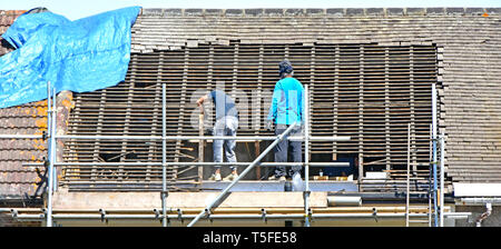 Builder workers on scaffolding removing roof tiles & timber in preparation for new dormer attic room in loft of terraced house Romford East London UK - Stock Photo