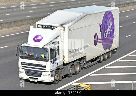 Looking down from above front & side of Gist hgv lorry truck & driver with articulated trailer & logo Transforming Supply Chain slogan on UK motorway - Stock Photo