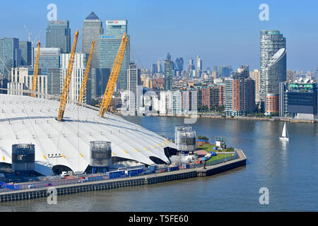 Aerial view at bend in River Thames sailing boat & London Canary Wharf cityscape skyline o2 arena dome roof Greenwich Peninsula London England UK - Stock Photo
