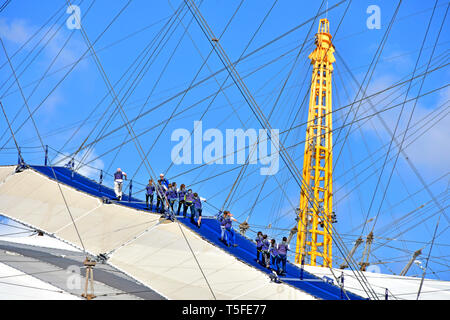 Up At The O2  millennium arena dome roof & rooftop  Skywalk walk group of people wear blue overalls climbing to top of o2 arena tour guide leader UK - Stock Photo