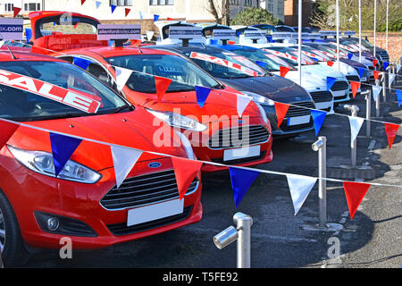Sale poster at Ford car dealership business forecourt display of used second hand red white & blue cars & bunting in dealer sales promotion England UK - Stock Photo