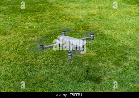 Birds eye view looking down onto a flying DJI Mavic 2 PRO personal Drone flying very low near to the ground - Stock Photo