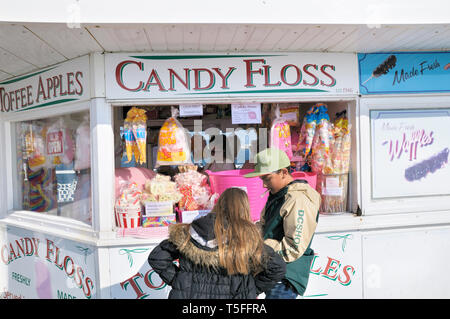 A young girl and boy counting small change money at a Candy Floss and confectionery stall on Brighton Palace Pier, East Sussex, England, UK