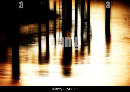 The dark pillars of a jetty and bridge in the evening light. - Stock Photo