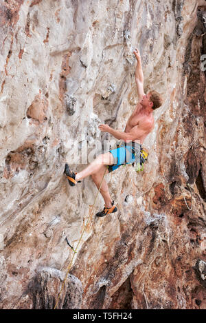 Thailand, Krabi, Lao Liang, barechested climber in rock wall - Stock Photo
