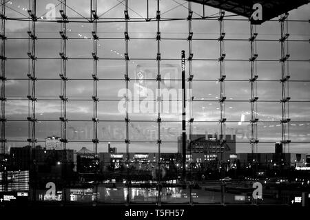 The glass front of the main railway station in Berlin with view of the skyline in the evening. - Stock Photo