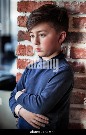 Mixed race Asian Caucasian boy with arms crossed wearing blue turtleneck shirt in front of red brick wall - Stock Photo