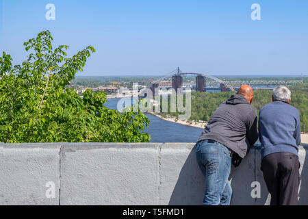 People relaxing on the viewing platform in Kiev Ukraine. View from the observation platform Friendship of Peoples to the old part of the city - Stock Photo