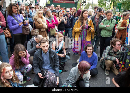 Climate change activists from the Extinction Rebellion group sing songs as police begin talking to and trying to clear Oxford Street near to the Marble Arch camp in protest that the government is not doing enough to avoid catastrophic climate change and to demand the government take radical action to save the planet, on 24th April 2019 in London, England, United Kingdom. Extinction Rebellion is a climate change group started in 2018 and has gained a huge following of people committed to peaceful protests. - Stock Photo