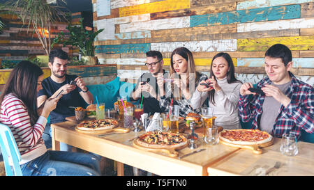 Social media addiction concept with young people photographing food in rustic restaurant – happy friends taking picture of pizza and hamburgers - Stock Photo