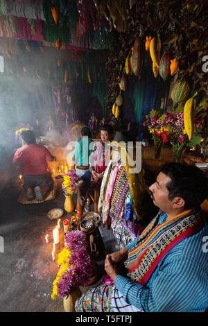 Local mayan people worshipping the image of Maximon, or San Simon, a traditional Mayan deity or folk saint, Santiago Atitlan Guatemala Central America - Stock Photo