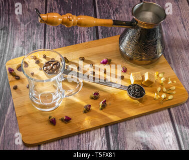 Measuring spoon for tea and coffee with coffee beans and dry tea leaves wth glass tea cup and copper cezve with orange wooden handle for Turkish coffe - Stock Photo