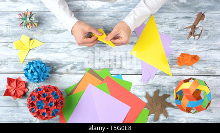 Making colourful origami flower. - Stock Photo